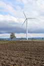 Spring landscape with wind turbine against a cloudy sky Royalty Free Stock Photo