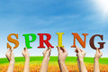 Spring letter of hold by group of people over colorful flowers background Stock Photos