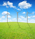 Spring meadow with wind turbines against the blue sky Stock Images