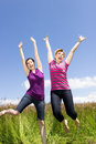 Spring pleasure two girlfriends jumping happily on a green meadow Royalty Free Stock Photos