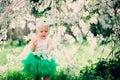 Spring portrait of cute baby girl in green skirt enjoying outdoor walk in blooming garden Royalty Free Stock Photo