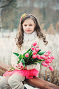 Spring portrait of smiling child girl with tulips bouquet on the walk Royalty Free Stock Photo
