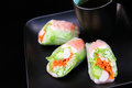 Spring rolls with tea on black japanese sushi salad plate Royalty Free Stock Photos