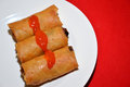 Spring rolls three with chili sauce on a white plate Royalty Free Stock Photography
