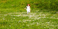 Spring run adorable year old girl running through a field of flowers Stock Photos