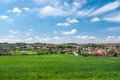 Spring rural scenery landscape with lush green wheat with typical european village in the background Stock Photo