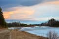 Spring sunset on the river that flows beneath the cliffs. Blue ice on the river. Royalty Free Stock Photo