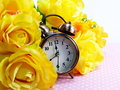 Spring time with alarm clock and artificial flowers bouquet background Royalty Free Stock Photo