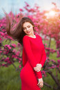 Spring touch. Happy beautiful young woman in red dress enjoy fresh pink flowers and sun light in blossom park at sunset. Royalty Free Stock Photo