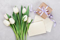 Spring tulip flowers, gift box and paper card on gray stone table from above in flat lay style. Greeting for Womens or Mothers Day