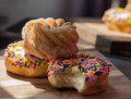Sprinkle donut two donuts and a honey cruller stacked on a cutting board Royalty Free Stock Photography