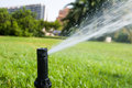 Sprinkler spraying water closeup of over grass in city park valencia spain Stock Photos