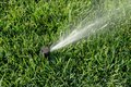 Sprinkler system working on fresh green grass automatic sprinklers watering grass Stock Photo