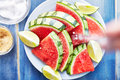 Sprinkling salt on pile of watermelon slices shot from overhead Royalty Free Stock Image