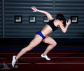 Sprinter woman leaps from starting block Stock Photo
