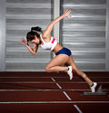 Sprinter woman leaps from starting block Stock Photography