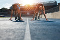 Sprinters at starting blocks ready for race athletes position on athletics stadium track with sun flare Stock Images