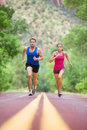 Sprinting running couple on road exercising sport young mixed race concentrated outside in nature jogging pretty asian model and Stock Image