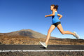 Sprinting running woman female runner training outdoors jogging on mountain road in amazing landscape nature fit beautiful fitness Royalty Free Stock Images