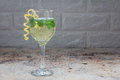 Spritzer cocktail with white wine, mint and ice, decorated with spiral lemon zest,  copy space Royalty Free Stock Photo
