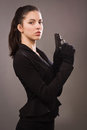 Spy girl in a black with gun coat Stock Photography