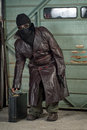 Spy or terrorist in ski mask with briefcase a masked type character leather trench coat bends to pick up a Royalty Free Stock Photography