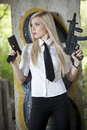 Spy with two guns female in shirt and tie standing at the wall Stock Image