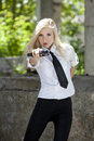 Spy woman with gun in white blouse and tie aiming a handgun Royalty Free Stock Photography