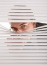 Spying a young man looking through window blinds Royalty Free Stock Image
