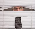 Spying a young man looking through window blinds Royalty Free Stock Images