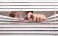 Spying a young man looking through window blinds Stock Image