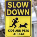 Square Black and yellow Slow Down Kids And Pets At Play sign against gray wooden pole Royalty Free Stock Photo