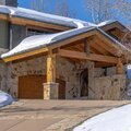 Square crop Home in Park City Utah with snowy gable roofs stone wall and outdoor stairs Royalty Free Stock Photo