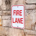 Square frame Fire Lane sign on stone retaining wall amid thick fresh snow on a hill in winter Royalty Free Stock Photo