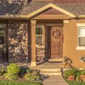Square frame Home with pathway leading to gabled entrance of the front porch with brown door Royalty Free Stock Photo