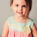Square indoor portrait in pastel tones of cute smiling child girl pink and mint dress Royalty Free Stock Photos
