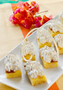 Square mini sponge cakes with merengue Stock Image