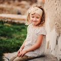 Square outdoor portrait in pastel tones of cute smiling child girl sitting by stone wall Stock Photo
