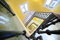 Square spiral staircase with handrail yellow walls windows Royalty Free Stock Photo
