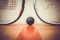 Squash ball between two squash rackets Royalty Free Stock Photo
