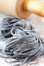 Squid ink pasta homemade fresh black tagliolini nests Stock Image