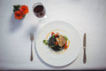 Squid ink spaghetti dish with basil with flowers and red wine Royalty Free Stock Photo