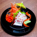 Squid sashimi in black plate on wood table Stock Images