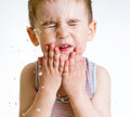 Squint little child washing face on white Royalty Free Stock Image