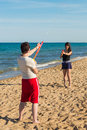 Squirt gun couple having fun on the beach with guns Royalty Free Stock Photo
