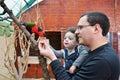 Stående av den lyckliga fadern och hans matande papegoja för dotter Arkivfoto
