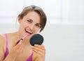 Stående av den lyckliga unga kvinnan som applicerar makeup Royaltyfri Foto