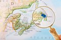 St john s newfoundland through a loop blue tack on map of canada with magnifying glass looking in on in the maritme provinces in Stock Photo