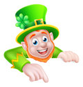 St patricks day cartoon leprechaun pointing character peeking above a sign and down at it Stock Photography