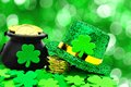 St patricks day decor pot of gold hat and shamrocks over a green background Stock Photo